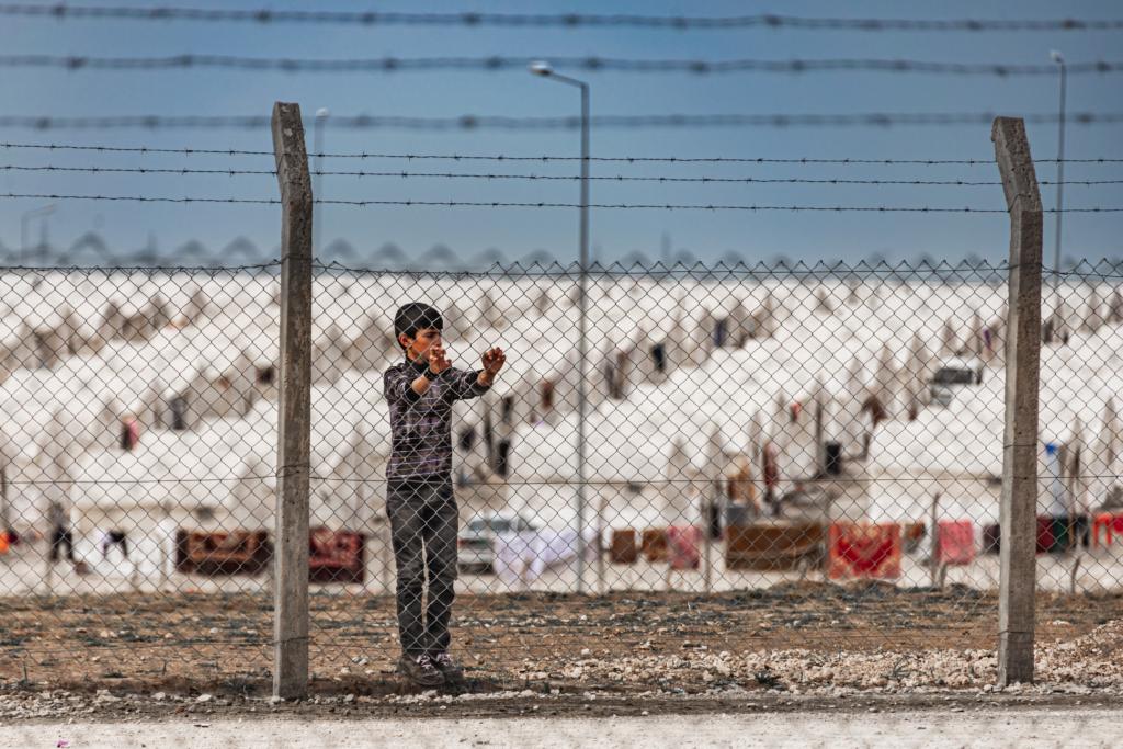 dziecko za płotem z drutem kolczastym na tle obozu uchodźców w Iraku
